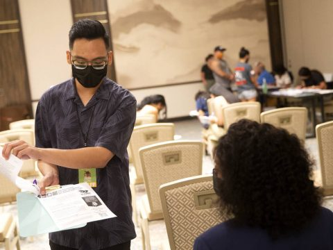 Lauro Solomo, community health worker with Immunize Nevada, shares paperwork with Jessica Dula, ...
